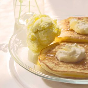 Amerikanske pandekager med is To lune amerikanske pandekager med to kugler is, flødeskumstoppe og sirup.